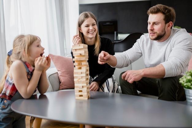 Família feliz jogando jenga Foto gratuita