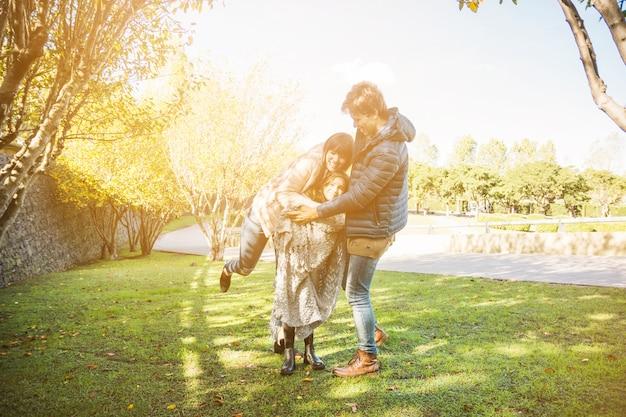 Família feliz jogando no parque em dia ensolarado Foto gratuita