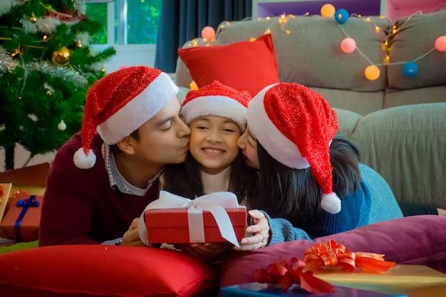 Família feliz. mãe e pai beijam a filha na sala de estar em casa no feriado de natal Foto Premium