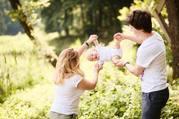 Família feliz. mãe e pai se divertir com seu filho pequeno, descansando em um parque verde de verão Foto gratuita