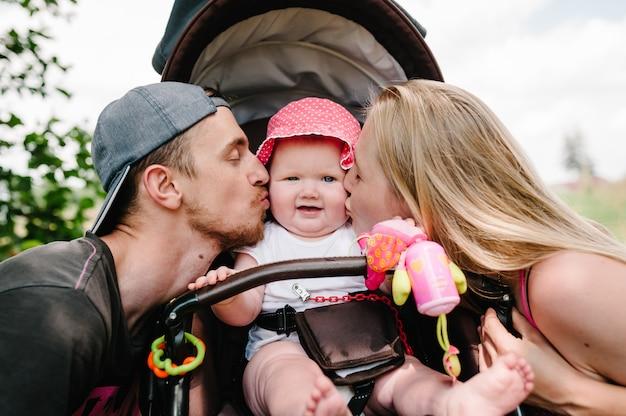 Família feliz: mãe, pai beijando garota no carrinho de bebê. Foto Premium