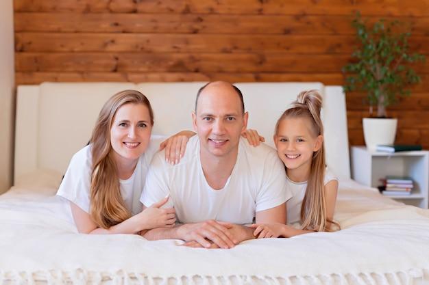 Família feliz, mãe, pai e filha na cama em casa no quarto Foto Premium