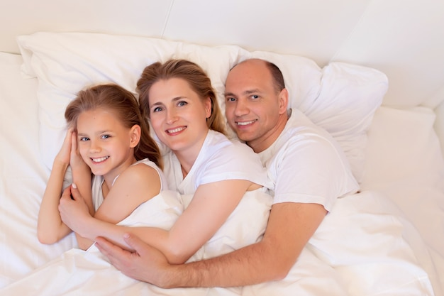 Família feliz, mãe, pai, filha dormir na cama no quarto em casa Foto Premium