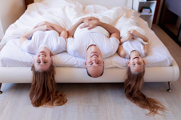 Família feliz, mãe, pai, filha rindo na cama no quarto em casa Foto Premium