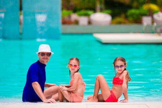 Família feliz na piscina Foto Premium