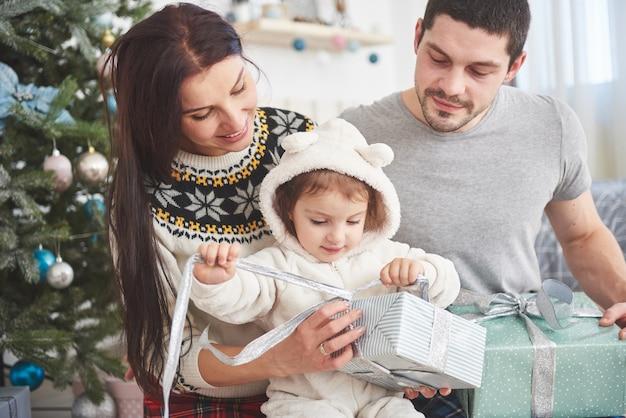 Família feliz no natal na manhã abrindo presentes juntos perto da árvore do abeto. o conceito de felicidade e bem-estar da família Foto Premium