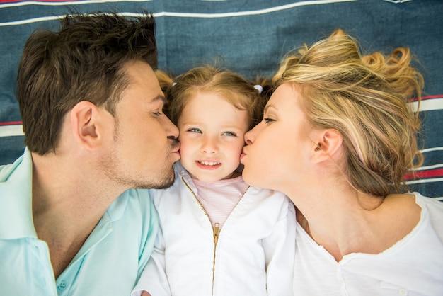 Família feliz nova que beija a menina Foto Premium
