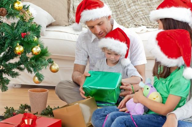 Família feliz olhando o menino abrindo um presente de natal Foto Premium