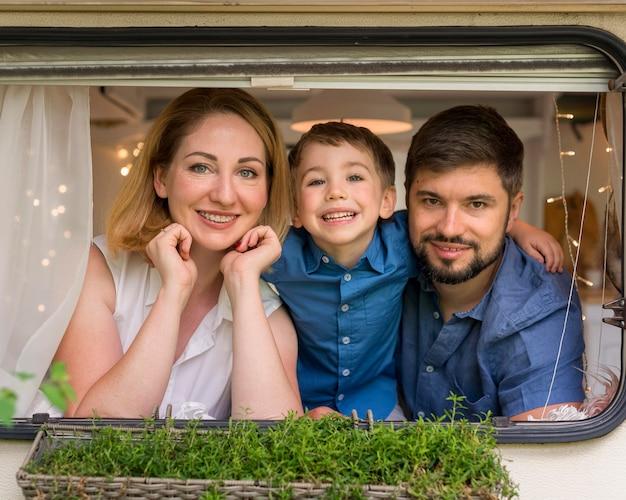 Família feliz olhando pela janela de um trailer Foto gratuita