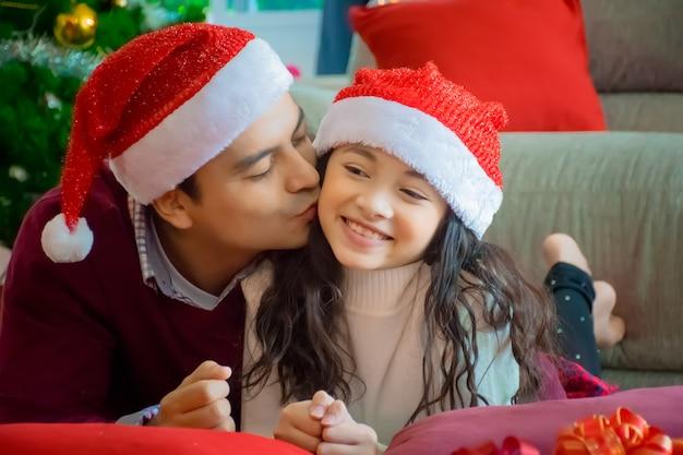 Família feliz. pai beija a filha na sala de estar em casa no feriado de natal. Foto Premium