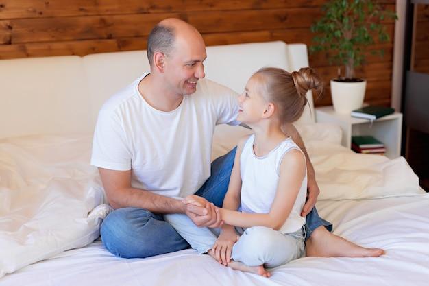 Família feliz, pai e filha abraçando na cama. feliz dia dos pais Foto Premium