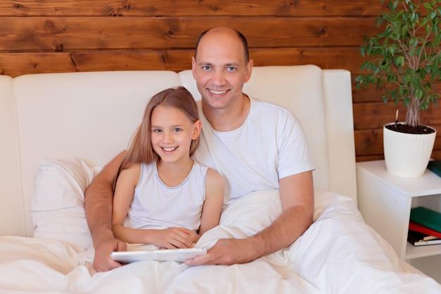 Família feliz, pai e filha conversando sobre o tablet em casa na cama. ensino à distância. Foto Premium