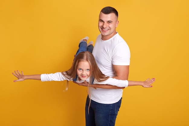 Família feliz pai e filha, filho desses denim onalls fingindo ser avião com as mãos se espalhando para o lado e se divertindo com o pai dela, isolado na parede amarela Foto gratuita
