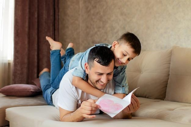 Família feliz, pai e filho estão deitado no sofá. Foto Premium