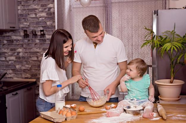 Família feliz, pai, mãe e filha brincam e cozinham na cozinha, amassam a massa e assam biscoitos. Foto Premium