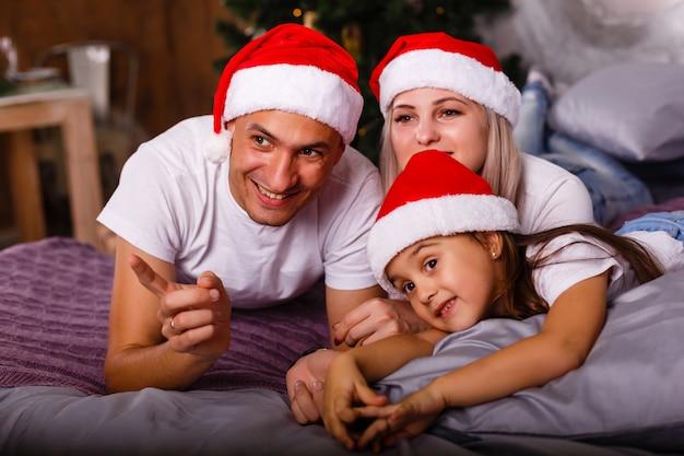 Família feliz perto da árvore de natal. criança, mãe e pai se divertindo em casa Foto Premium