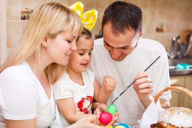 Família feliz, pintando ovos de páscoa na mesa da cozinha Foto Premium