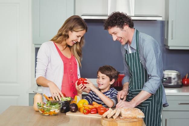 Família feliz, preparando uma salada de legumes Foto Premium