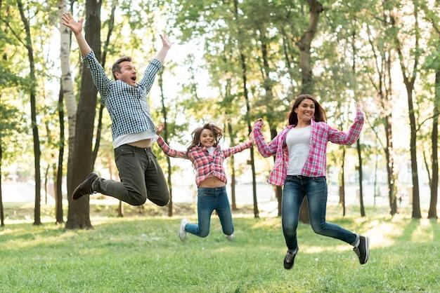 Família feliz pulando na natureza verde Foto gratuita