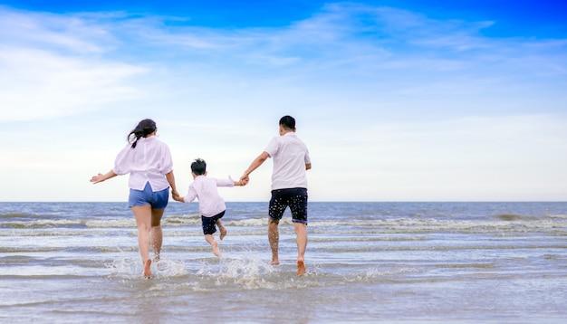 Família feliz pulando na praia Foto Premium
