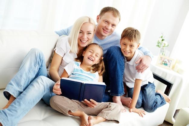 Família feliz que lê um livro Foto gratuita