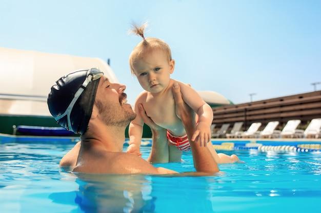 Família feliz se divertindo à beira da piscina. Foto gratuita