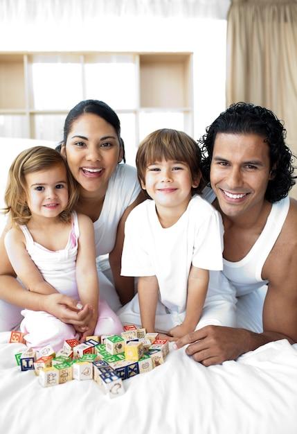 Família feliz se divertindo com brinquedos cubos Foto Premium