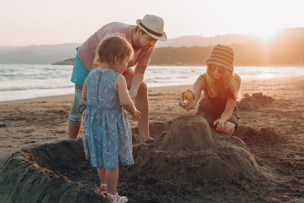 Família feliz se divertindo juntos na praia ao pôr do sol. castelo de areia de construção Foto gratuita