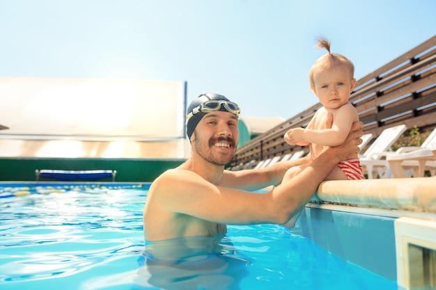 Família feliz se divertindo na piscina Foto gratuita