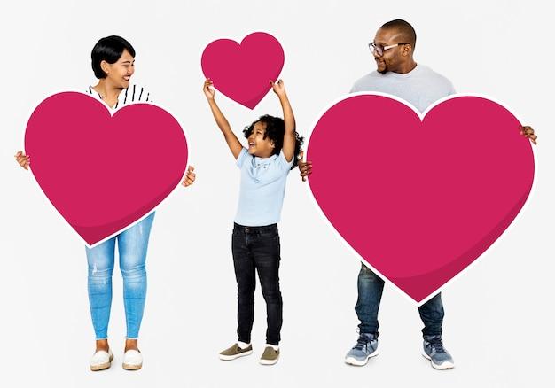 Família feliz segurando ícones de coração vermelho Foto gratuita