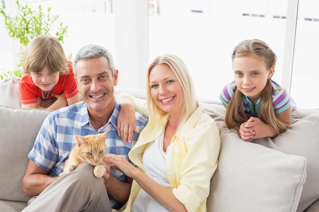 Família feliz sentada com gato no sofá em casa Foto Premium