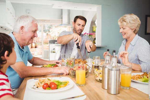 Família feliz sentado na mesa de jantar Foto Premium