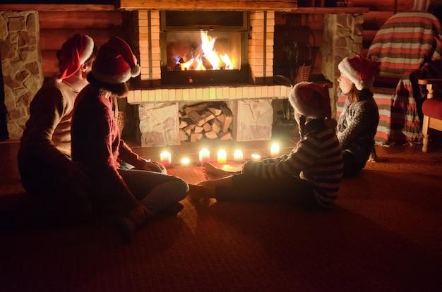 Família feliz sentado perto da lareira em casa e comemorando o natal e ano novo, pais e filhos em chapéus de papai noel Foto Premium