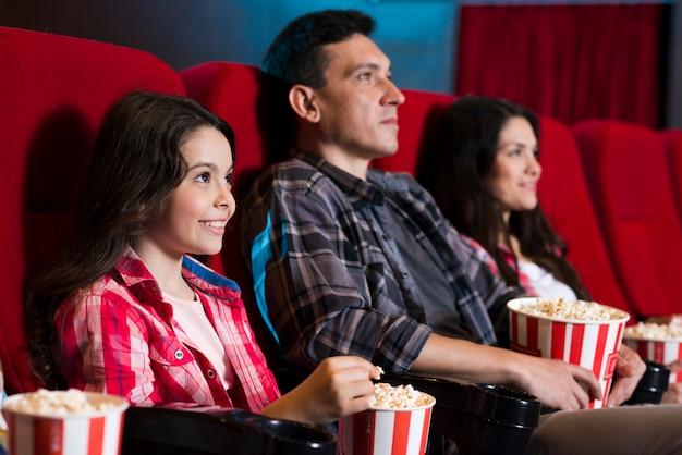 Família feliz, sentando, em, cinema Foto gratuita