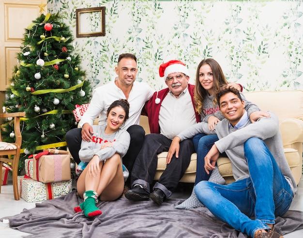 Família feliz, sentando, perto, árvore natal Foto gratuita