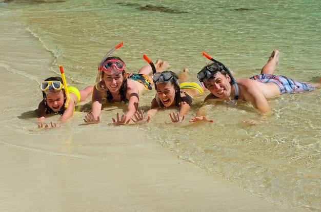 Família feliz snorkeling e se divertindo nas férias de praia tropical Foto Premium