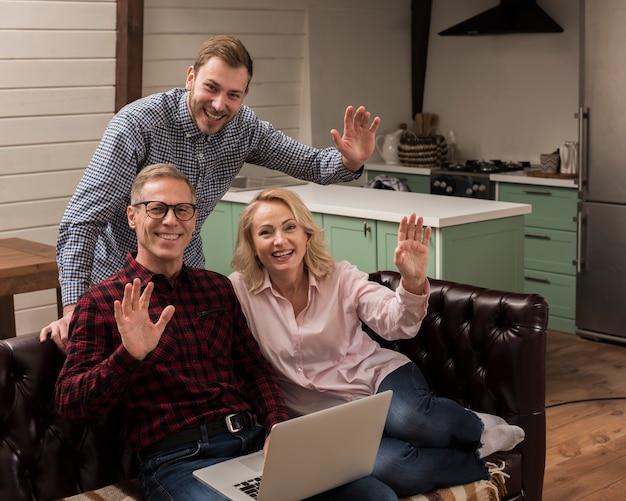Família feliz sorrindo e acenando na cozinha Foto gratuita