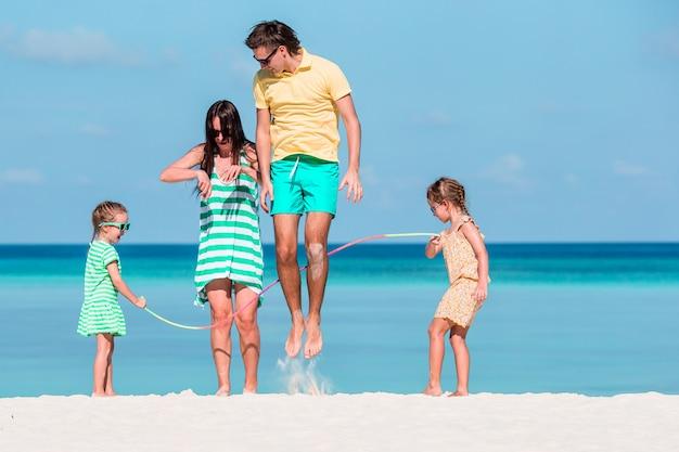 Família feliz tocando juntos na praia branca Foto Premium
