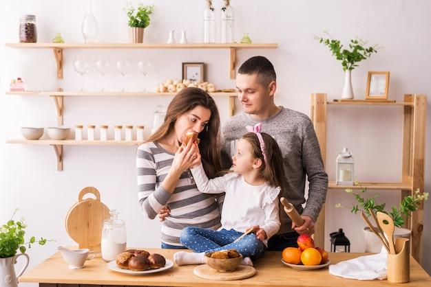 Família feliz tomando café da manhã com torradas na cozinha Foto Premium