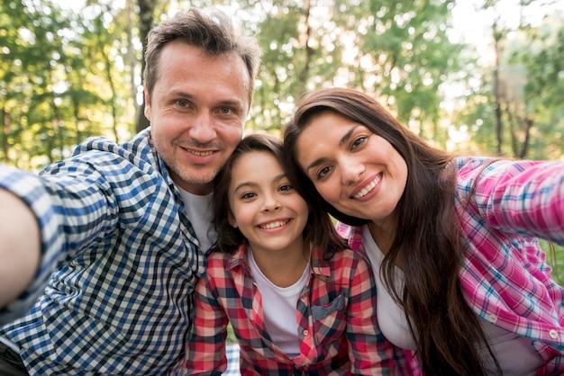Família feliz tomando selfie no parque Foto gratuita