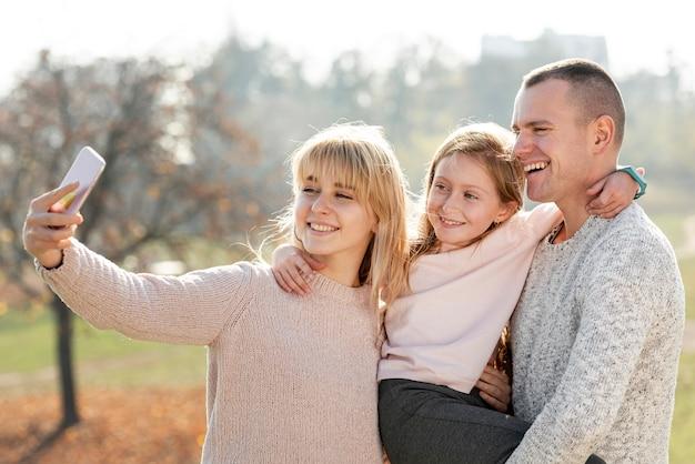 Família feliz tomando uma selfie na natureza Foto gratuita