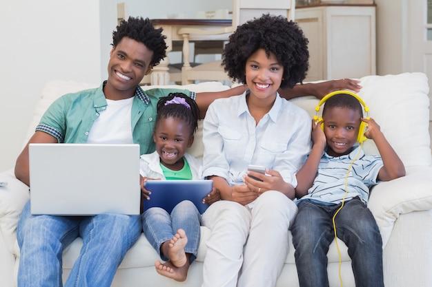 Família feliz usando tecnologias no sofá Foto Premium