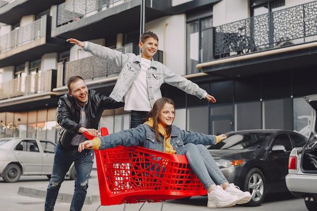 Família fofa brincando com um carrinho de compras em uma cidade Foto gratuita