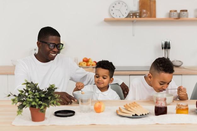 Família fofa comendo juntos na cozinha Foto gratuita