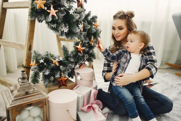Família fofa sentado perto da árvore de natal Foto gratuita