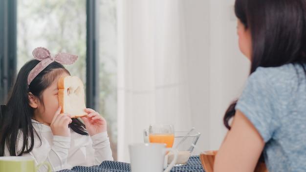 Família japonesa asiática toma café da manhã em casa. a filha asiática escolhe e joga o sorriso de riso do pão com os pais ao comer flocos de milho cereal e leite na bacia na tabela na cozinha moderna de manhã. Foto gratuita