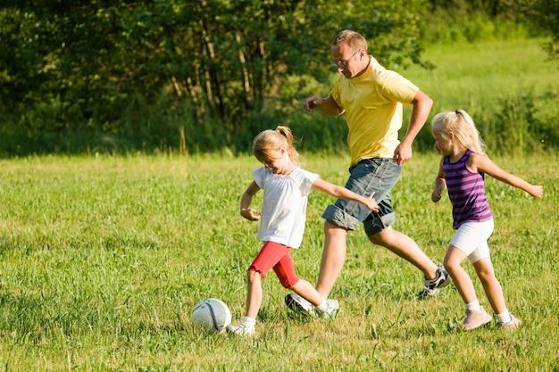 Família jogando futebol em um campo de grama Foto Premium