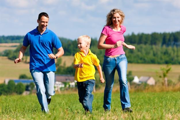 Família jogando tag no prado no verão Foto Premium