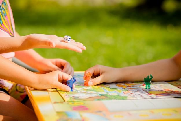 Família jogando um jogo de tabuleiro, uma criança está em movimento e capturando o pedaço de outro player.games no jardim de infância. jogo de tabuleiro e conceito de lazer de crianças. crianças segurando pessoas vermelhas figura na mão Foto Premium