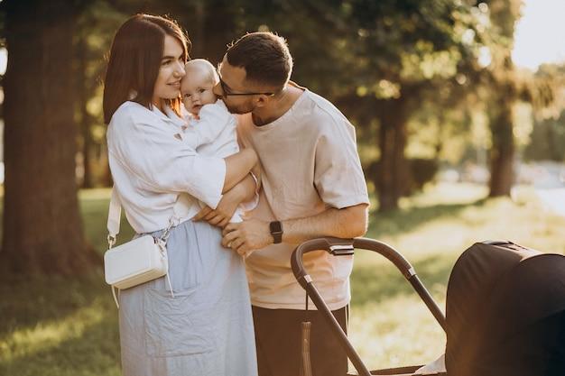Família jovem caminhando com bebê no parque Foto gratuita